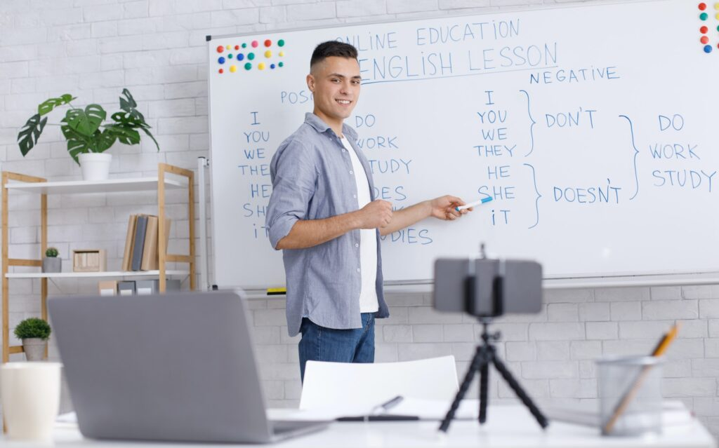 Online tutor remote. Smiling young man points to whiteboard, looks at webcam